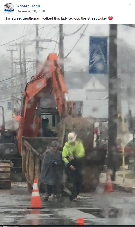 Photo of John Decker assisting a woman in the rain.